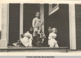 Children on porch with toys, Seward, Alaska, ca. 1905-1915.
