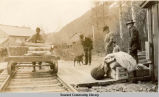 Man with handcar on railroad tracks.