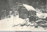 Log cabin in snow storm, ca. 1910.