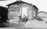 Man sitting on the front steps of a log cabin.