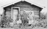 Man and two women standing in front of a log cabin at Tanana