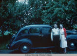 Man and woman pose in front of car.