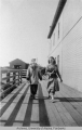 Two women walk along a boardwalk