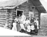 Group of young girls in front of log cabin