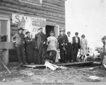 Group standing in front of a log saloon