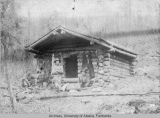 Four men pose outside of a log cabin
