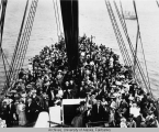 Large crowd on the deck of a ship.