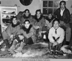 Group of men sitting on a couch and a caribou skin rug
