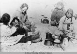Alaska Native women sitting on the ground.