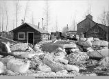 Jumbled river ice from Fairbanks flood of 1911 in front of log cabins.