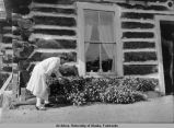 Woman tending flowers outside a log cabin.
