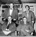 Four men in front of a bookcase