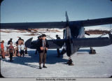 Man poses beside plane.