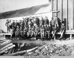 Miners in front of tin building.