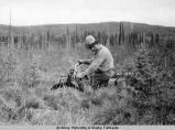 Slim riding a bucking two-wheeler through the muskeg.