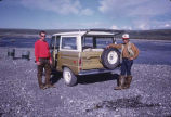 Two men stand by Land Rover.
