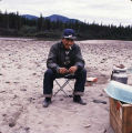 Native Alaskan man on folding stool.