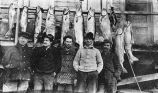Men standing in front of fish.