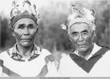Two Native men in ceremonial dress.