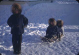 Little kids sitting on sled.