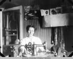 Cora Rivenburg seated behind a sewing machine