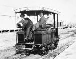 Three men on a railroad trolley.