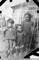 Three of Young Adam's children in front of a fence