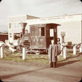 Man in front of railroad locomotive.