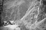 Two automobiles near waterfall.