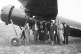 Group of people in front of an airplane.