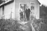 Two men in front of a house.