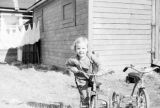 Little girl on a tricycle.