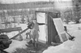 Woman standing outside an outhouse.