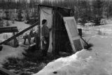 Woman outside an outhouse.