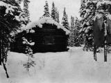 Log cabin covered in snow.