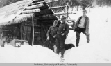 Three men standing in snow outside log cabin