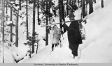 Three people carrying large backs through the snow