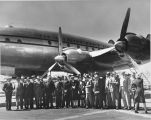 Group photo taken next to commercial aircraft.