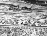 Aerial view landing field, hangars and other buildings.