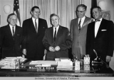 Governor Egan behind his desk with men.