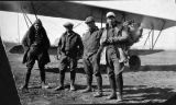 Four men in front of an airplane.