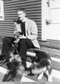 Rev. Rowland Cox seated on steps with puppies