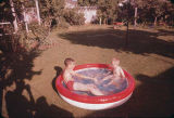 Boys in a portable pool.