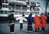 Alaska Native dancers performing on a pier.