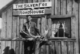 Man in uniform in front of [The Silver Fox] Roadhouse next to horns [antlers].