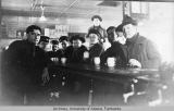 Soldiers gathered around a bar, some holding mugs.