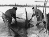 Two women setting net in hole cut in river ice.