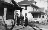 Fannie Quigley and couple standing in front of a house.