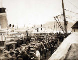 Soldiers waiting on a dock to board a steamship.