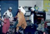 Benny & The Beatniks perform air guitar for elementary students.